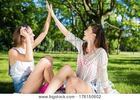 Happy Female Friends Doing High Five Outside