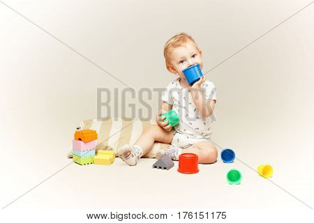 Studio shot of an adorable baby boy sitting on the floor and playing with some toys.