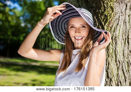 Happy Young Woman In Hat Leaning Against Tree Outside