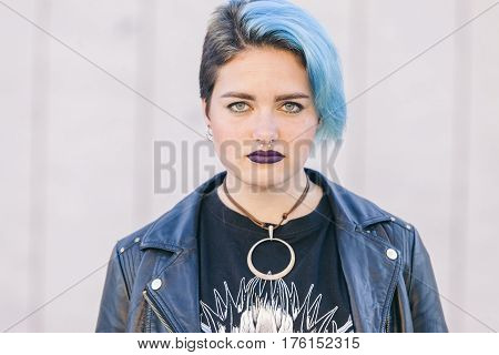 portrait of a young punk woman with blue eyes and dark leather clothes isolated on the street