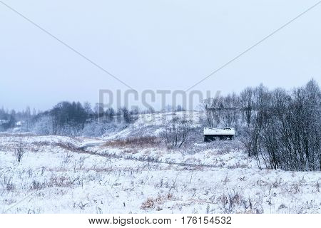 Wooden abandoned house with broken roof on the bank of a small river. Winter dull landscape.
