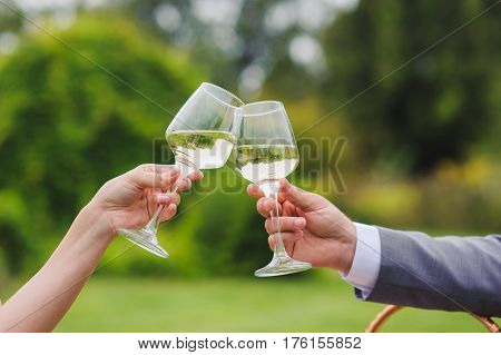 Couple drinking white wine outdoors. Clinking glasses. Grass trees and bushes in the background.
