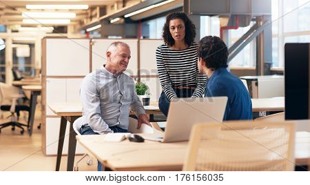 Diverse group of casually dressed professional colleagues talking business together while having a meeting at a desk in a modern office