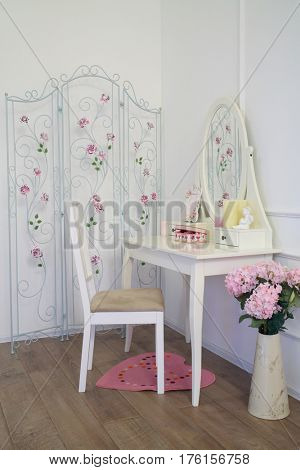 Interior female room with dressing table, chair, screen and flowers