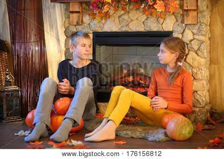 Young girl and boy sitting in the room with pumpkins near a fireplace