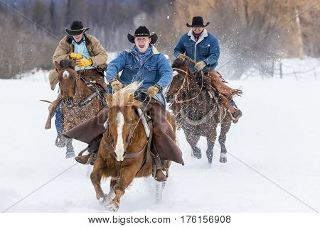 Cowboys round up a herd of horses as they're running through the snow in the mountains