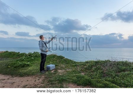 Man holds a drone before the flight. For video on the sea.