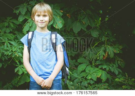 Happy schoolboy with a backpack going to school. Outdoor. Education, back to school, people concept