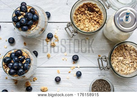 healthy breakfast with blueberry yogurt dessert granola chia seeds oats and milk on white wooden table. top view