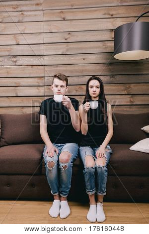 Cute couple sitting on a brown couch, sadly looking into the camera and drinking hot tea. concept of a first date or modest people