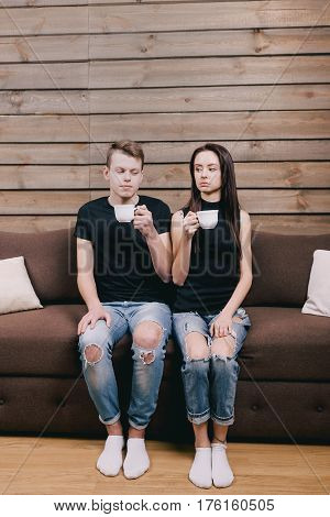 sad couple sitting on a brown sofa, look askance at each other and drinking hot coffee. Concept of divorce or family quarrel