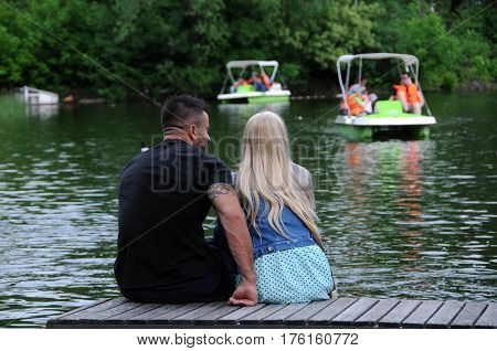 MOSCOW RUSSIA - MAY 31 2015: Caucasian couple sits on the wooden plank bridge by the water in Gorky park