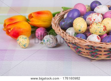 Easter candy and tulips on a colorful tabletop