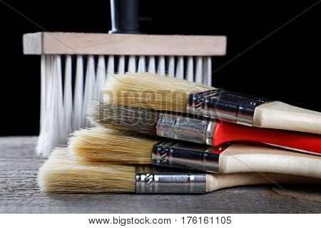 Paint brushes on a wooden table and a black background