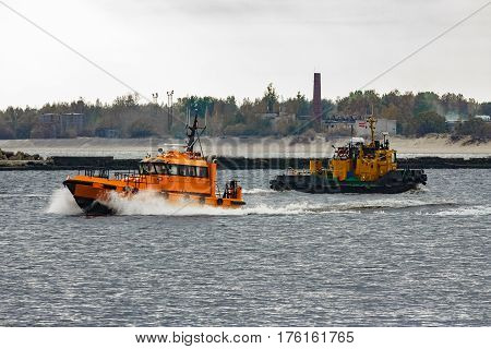 Orange pilot ship moving at speed past the tug ship in Riga