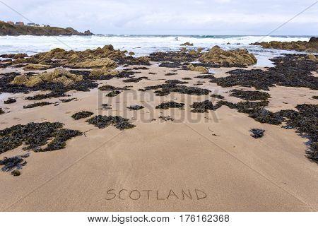 Scotland inscribed on wet yellow rocky beach sand.