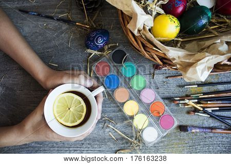 Childs Hand Holdind Cap Of Tea With Lemon And Next To Him Paints And Brush For Coloring Eggs For Eas