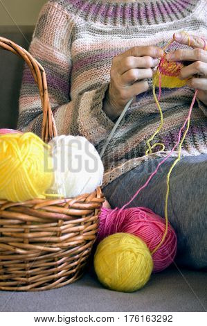 Women's  Hands Hold Knitting Needles And A Yellow Thread To Tie A Scarf From Them