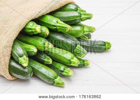 canvas sack full of zucchini on wood