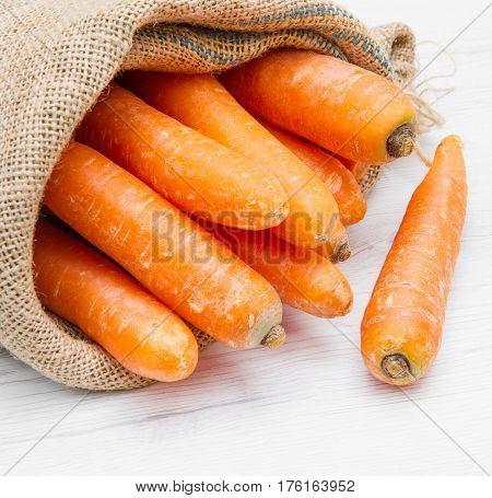 canvas sack full of carrot on white