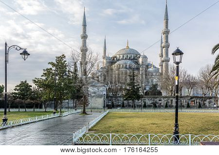 Blue Mosque on the cloudy sky background in Istanbul. In front of the mosque there is a foot road, trees, street lamps, lawns. Horizontal.