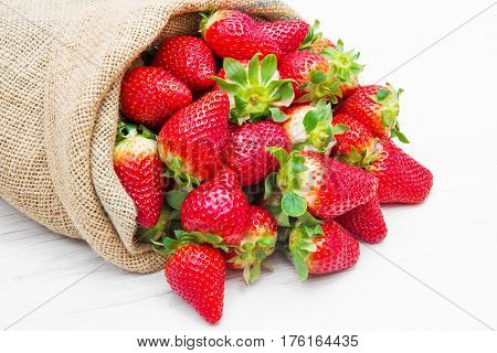 canvas sack full of red strawberry on wood