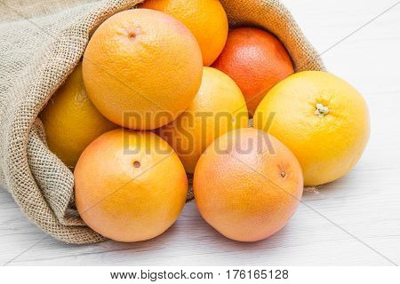 a canvas sack full of grapefruit on wood