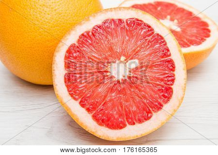 a group of fresh grapefruit on white wood