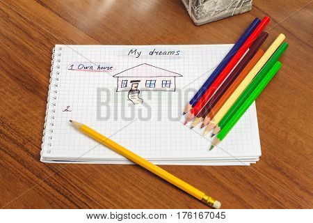 My dream own house written text and drawing on the notepad color pencils on the table. concept of visualization future