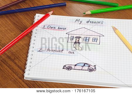 My dream own house and personal car written text and drawing on the notepad color pencils on the table. concept of visualization future