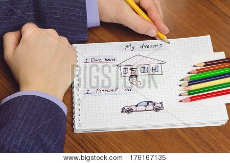 Man writes and draws own dream of house and personal car on the notepad with color pencils. concept of visualization future