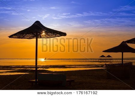 Sunrise at the sea with silhouette of beach umbrellas in Egypt, Red sea