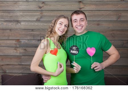 Smiling love couple shows funny icons on a sticks
