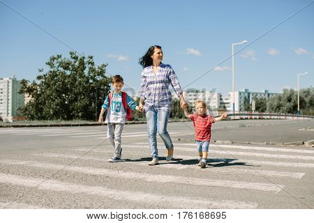 Mother and her children crossing a road on way to school in the morning