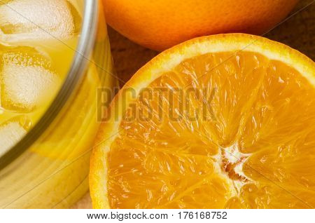 Freshly Cut Orange With Glass Of Juice And Ice Cubes On Wood
