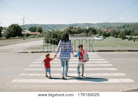 Mother and her children walking to school in the morning