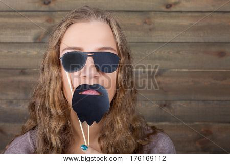 Woman with funny sunglasses and beard on a stick