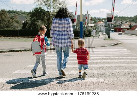Mother holding her children and crossing a road on way to school