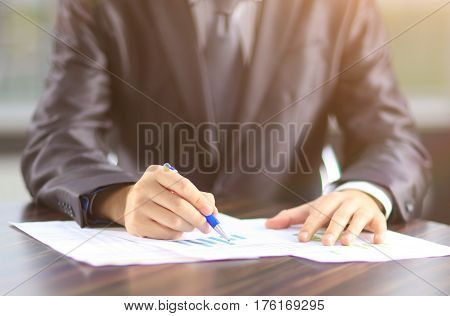 closeup of businessman with pen adjusts financial charts