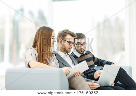 employees with a laptop sitting in the lobby of the office.the photo has a empty space for your text.