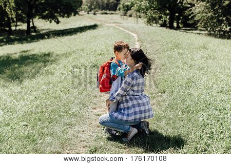 Little schoolboy kissing and hugging his mother saying goodbye to her