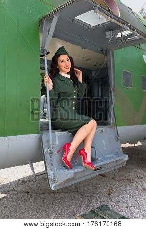 Sexy pin-up model in WW2 uniform posing against old-timer aircraft