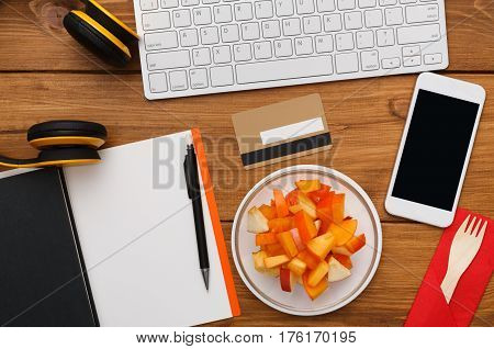 Healthy business lunch at workplace. Top view flat lay of desktop - laptop, notepad, credit card and phone on wooden desk background with plate of fruit salad snack, nobody, objects