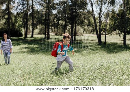 Happy schoolboy on his way to school running away from his mother