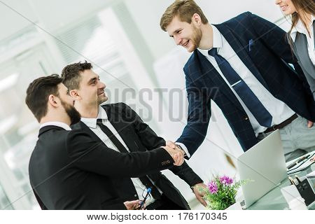 closeup of a successful handshake business partners after signing the contract in the workplace in a modern office