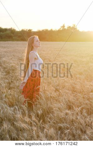 Girl in wheat field standing arms outstretched at sunset and enjoy the outdoors side view
