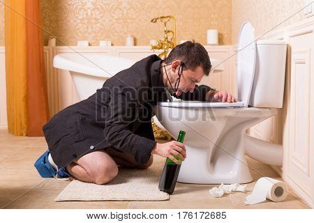 Drunk man with bottle of wine sick in toilet bowl