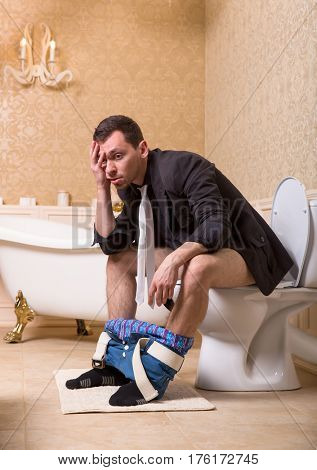 Drunk man with pants down sitting on toilet bowl