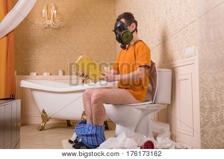 Man in gas mask sitting on toilet and reading book