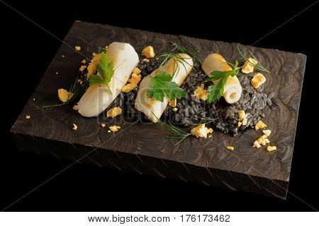 Black squid ink risotto with lightly seared calamary on wooden board, isolated on black